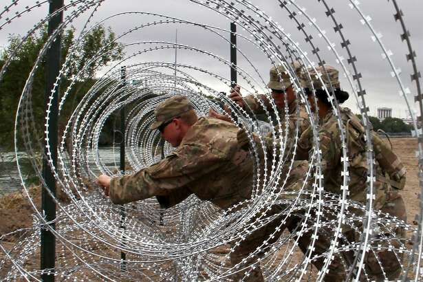 """(FILES) In this file photo taken on November 18, 2018, Soldiers from the Kentucky-based 19th Engineer Battalion install barbed wire fences on the banks of the Rio Grande in Laredo, Texas. - US President Donald Trump said on April 24, 2019, the US is sending armed soldiers to the southern border after Mexican soldiers """"pulled guns"""" on US troops. """"Mexico's Soldiers recently pulled guns on our National Guard Soldiers, probably as a diversionary tactic for drug smugglers on the Border. Better not happen again! We are now sending ARMED SOLDIERS to the Border. Mexico is not doing nearly enough in apprehending & returning!"""" Trump said on Twitter. (Photo by Thomas WATKINS / AFP)THOMAS WATKINS/AFP/Getty Images"""