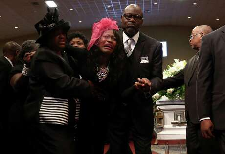 Roxane Freeman, center, is helped away from her husband's coffin during the funeral service at the Greater Grace Outreach Church on July 29, 2017, in Houston. Heywood Freeman and the couple's two children were killed in a crash July 21, 2017, along Beltway 8.