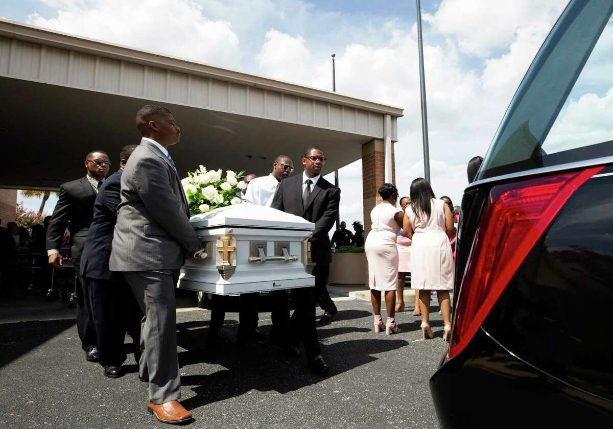 Pallbearers load Heywood Freeman's coffin into the hearse after the funeral service at Greater Grace Outreach Church on July 29, 2017, in Houston.