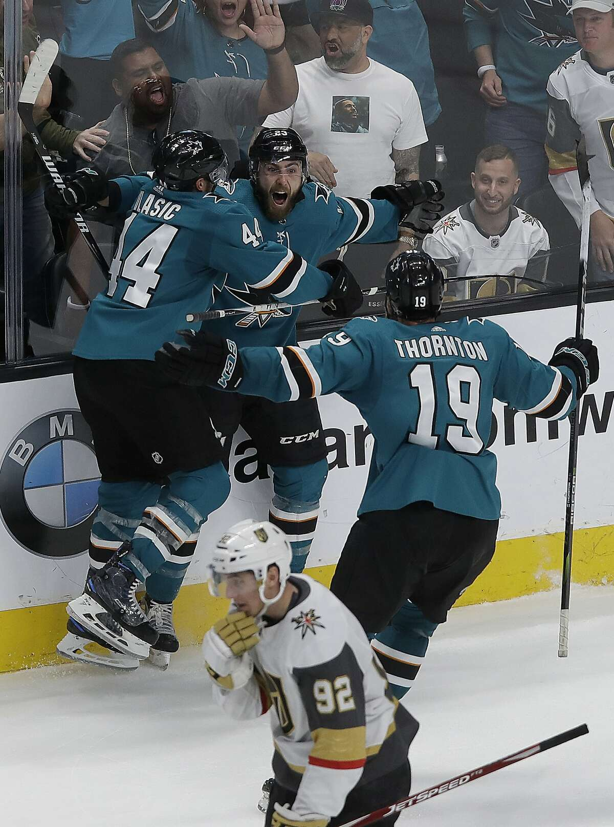 San Jose Sharks right wing Barclay Goodrow, center, is congratulated by defenseman Marc-Edouard Vlasic (44) and center Joe Thornton (19) after scoring the winning goal against the Vegas Golden Knights during overtime of Game 7 of an NHL hockey first-round playoff series in San Jose, Calif., Tuesday, April 23, 2019. Pictured at bottom is Golden Knights left wing Tomas Nosek (92). (AP Photo/Jeff Chiu)