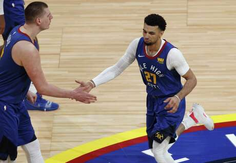 Denver Nuggets center Nikola Jokic, left, congratulates guard Jamal Murray after he scored a basket against the San Antonio Spurs in the second half of Game 5 of an NBA basketball first-round playoff series Tuesday, April 23, 2019, in Denver. The Nuggets won 108-90.