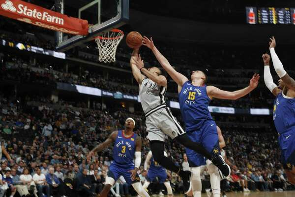 San Antonio Spurs guard Derrick White (4) and Denver Nuggets center Nikola Jokic (15) in the first half of Game 5 of an NBA basketball first-round playoff series Tuesday, April 23, 2019, in Denver.