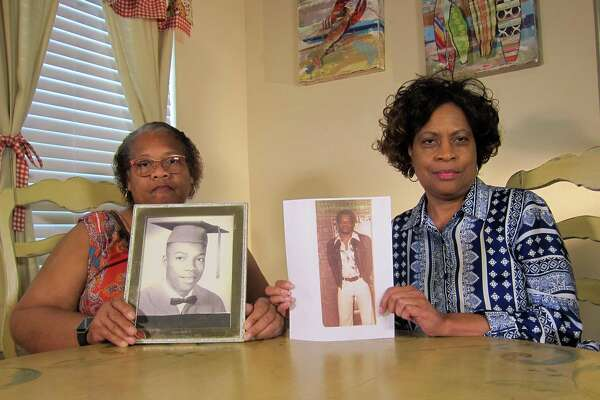 Mylinda Byrd Washington, 66, left, and Louvon Byrd Harris, 61, hold up photographs of their brother James Byrd Jr., who in 1998 was lynched in Jasper, Texas, by racists who chained him to a pickup truck and dragged him to death.