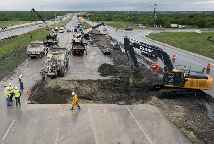 Crews work to repair a sinkhole caused by the collapse of a San Antonio Water System sewer line under U.S. 90 westbound near Hunt Lane on the far West Side. Drivers were routed to the access road on April 24, 2019.