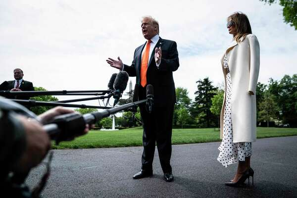 President Donald Trump, with first lady Melania Trump by his side, stops to talk to reporters and members of the media as he walks from the Oval Office to Marine One as they depart from the White House on Wednesday.