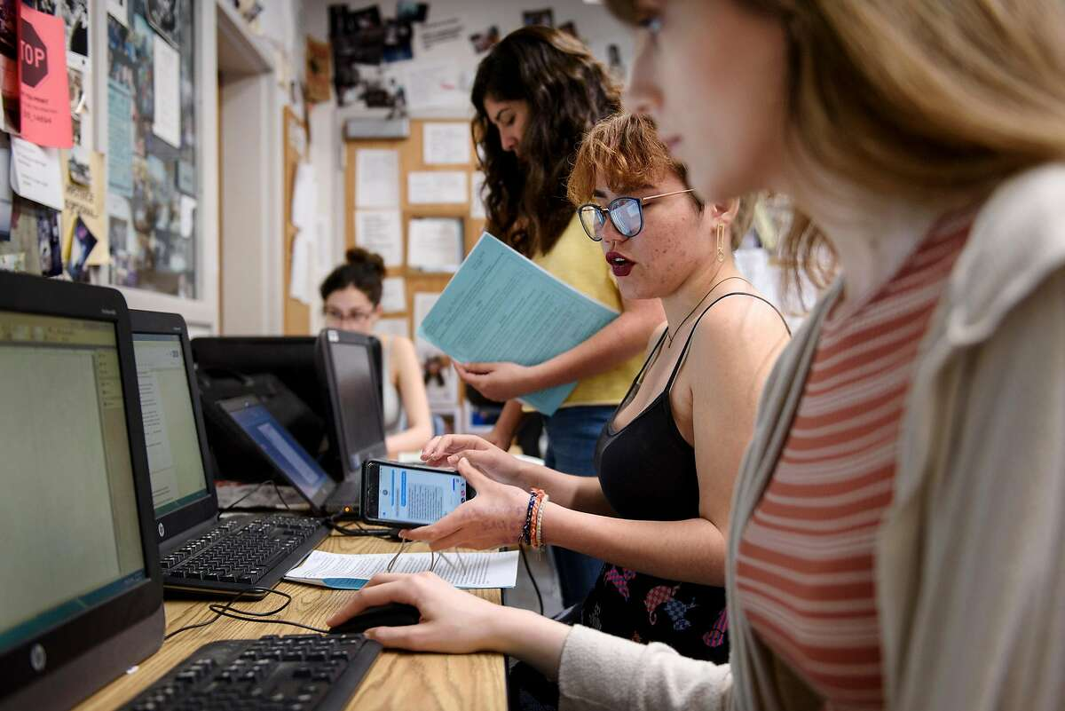 Journalism students Gabriella Backus, center, and Bailey Kirkeby design the layout of the Bruin Voice school paper at Bear Creek High School in Stockton, Calif, on Wednesday, April 24, 2019. The Stockton school district is threatening to fire Kathi Duffel, faculty adviser for the Bruin Voice student newspaper, if she doesn't show them a certain story in advance, violating the papers First Amendment freedom of the press rights.