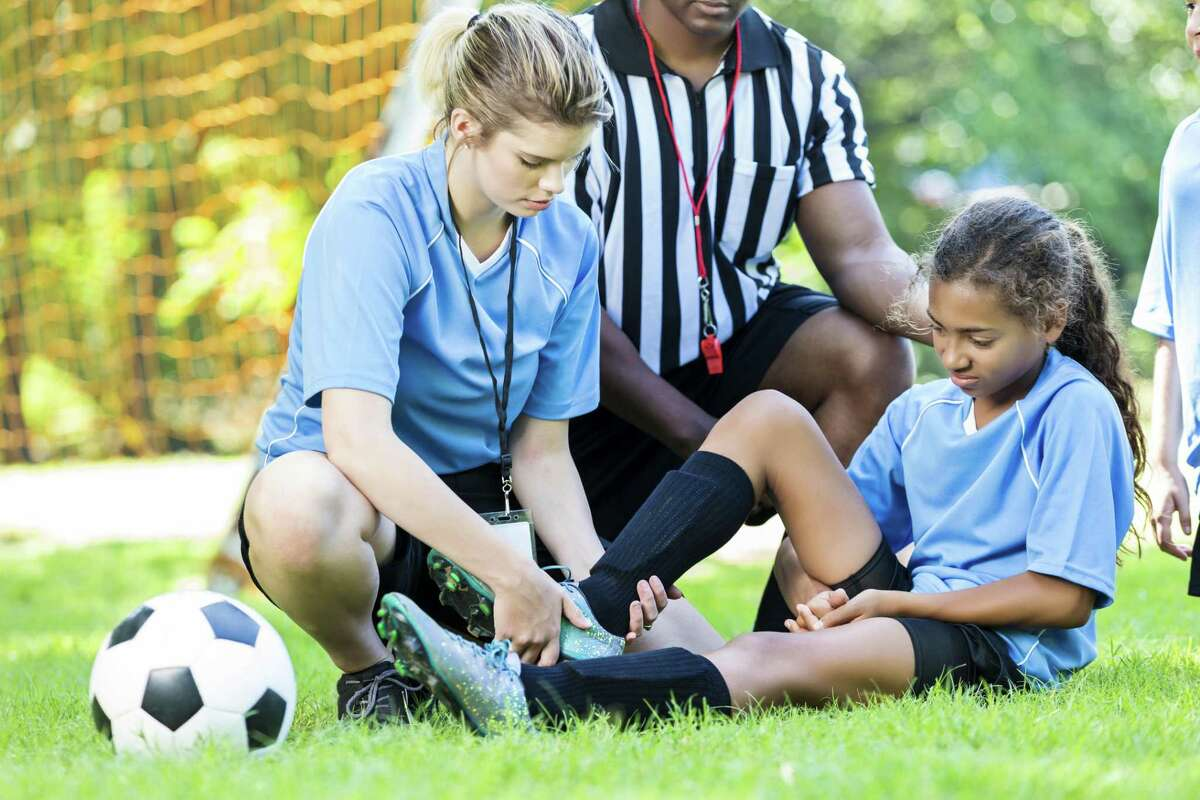 Injured girl soccer player, she is sitting on the grass and is getting her ankle checked out by the soccer coach. The referee is kneeling down with them. There is a teammate in the right side of the photograph who has taken a knee for her injured teammate. They are wearing light blue uniforms and black soccer shorts. There is a soccer ball by her feet.
