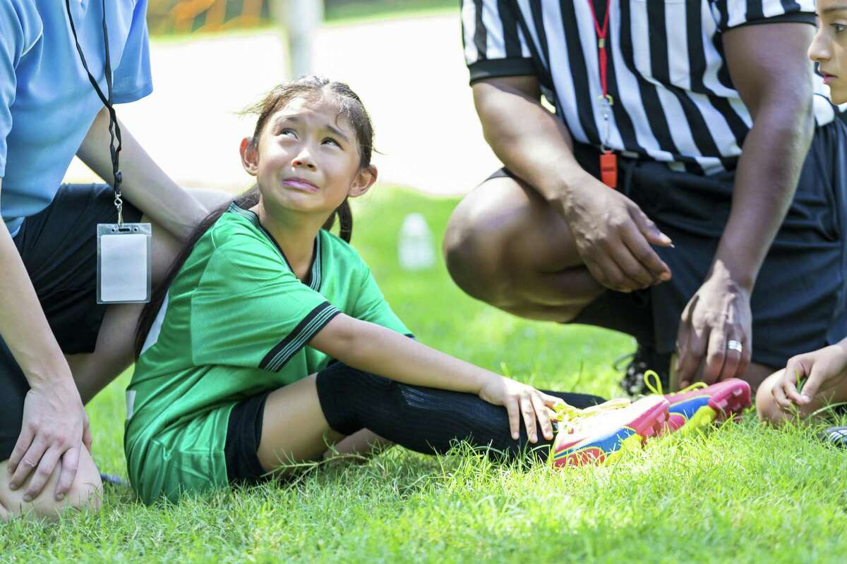 Pretty young female soccer player holds her ankle and grimmaces in pain while crying. She is sitting on the playing field with her coach and referee gathered around her. She has a sad expression on her face as she looks up at her female Caucasian coach. An African American referee is sitting beside her. The girl is wearing a green uniform and has black hair back in a ponytail. Her coach is wearing a blue jersey.