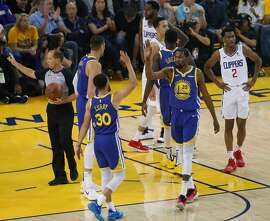 Golden State Warriors Stephen Curry and Kevin Durant high five in the first quarter during game 5 of the Western Conference Playoffs between the Golden State Warriors and the Los Angeles Clippers at Oracle Arena on Wednesday, April 24, 2019 in Oakland, Calif.