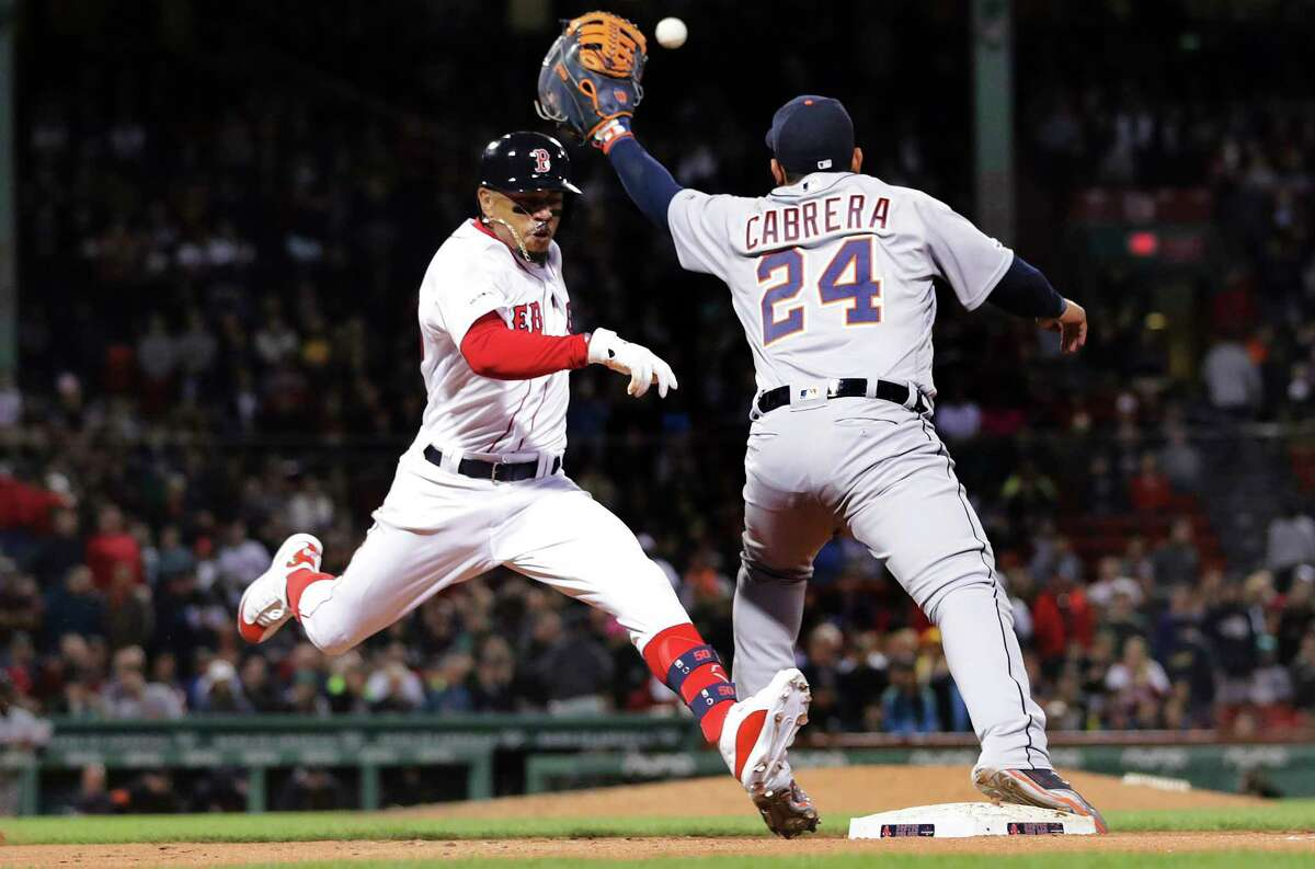 Boston Red Sox's Mookie Betts, left, legs out a single as Detroit Tigers first baseman Miguel Cabrera (24) catches the throw during the seventh inning of a baseball game at Fenway Park, Wednesday, April 24, 2019, in Boston. (AP Photo/Charles Krupa)