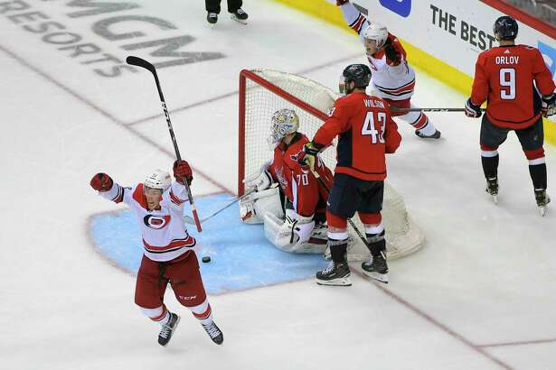 Hurricanes defenseman Jake Bean, left, celebrates his game-winning goal during the second overtime Wednesday night against the Capitals. Carolina defeated Washington, 4-3, to win the series.
