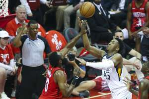 Utah Jazz guard Donovan Mitchell (45) shoots over Houston Rockets guard James Harden (13) during Game 5 of an NBA first round playoff series at Toyota Center in Houston, Wednesday, April 24, 2019.
