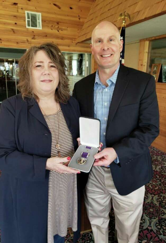 Congressman John Moolenaar presents Jan Hecht, the wife of late Vietnam War veteran Roger Hecht, with a Purple Heart on April 23, 2019. (Photo provided / David Russell)