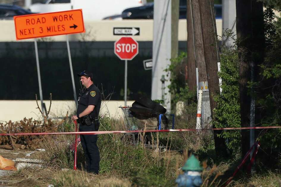 Houston Police Homicide detectives investigate the scene where a deceased body was found in a ditch on West 12th Street, near Penner Street Thursday, April 25, 2019, in Houston.