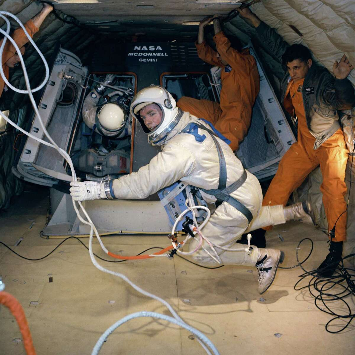 In this Feb. 18, 1966 photo, astronaut David R. Scott holds a maneuvering unit while suspended in a weightless state during extravehicular activity training in a C-135 Air Force plane.