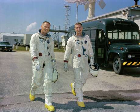 Astronauts Neil A. Armstrong (left), command pilot, and David R. Scott, pilot, of the Gemini 8 crew, are shown March 11, 1966 during a photo session outside the Kennedy Space Center's Mission Control Center. They both later stepped on the moon during the Apollo missions.