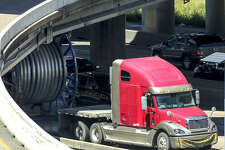 An 18-wheeler carrying a spool is stuck on Highway 59 after hitting the West Loop overpass Thursday, April 25, 2019, in Houston.