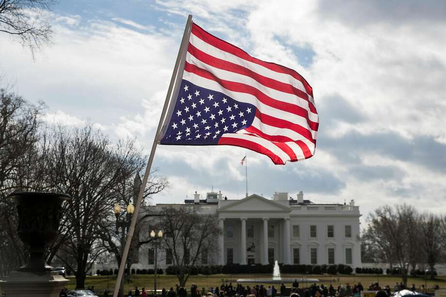 An upside-down U.S. flag, the national symbol for distress, is posted in February outside the White House, whose current occupant is blamed for some Americans' anxiety and uneasiness. Photo: Sarah Silbiger / New York Times
