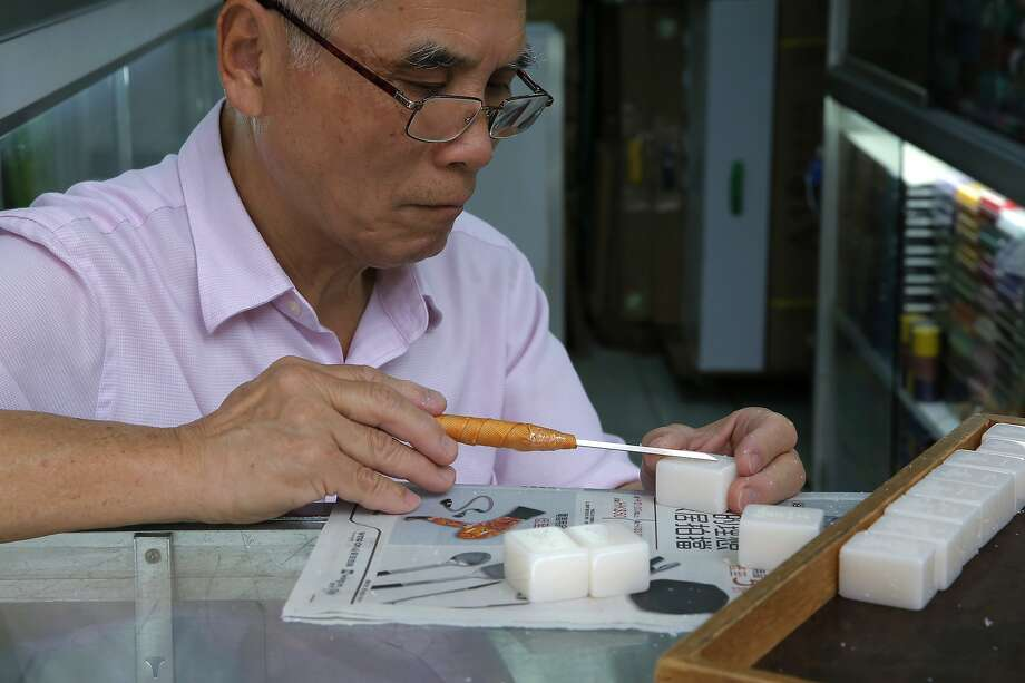 Cheung Shun-king, 65, engraves a character on a mahjong tile in his decades-old, 100-square-foot shop. Photo: Photos By Kin Cheung / Associated Press