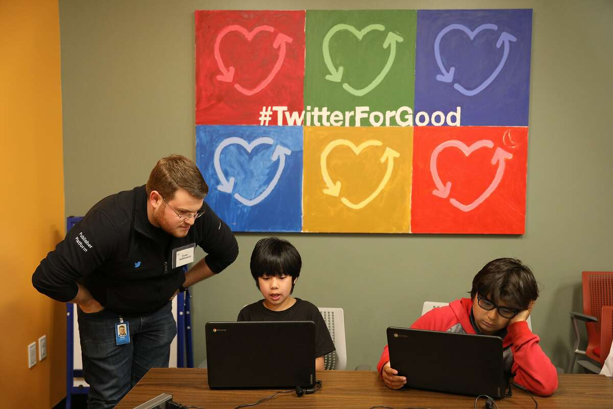 Evan Sobkowicz (l to r), Twitter software engineer, works with Jeffrey, 9, and Luca, 10, during an interactive coding workshop at Neighbor Nest on Thursday, March 21, 2019 in San Francisco, Calif.