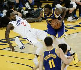 Los Angeles Clippers Patrick Beverley falls while defending against Golden State Warriors Draymond Green in the third quarter during game 5 of the Western Conference Playoffs between the Golden State Warriors and the Los Angeles Clippers at Oracle Arena on Wednesday, April 24, 2019 in Oakland, Calif.