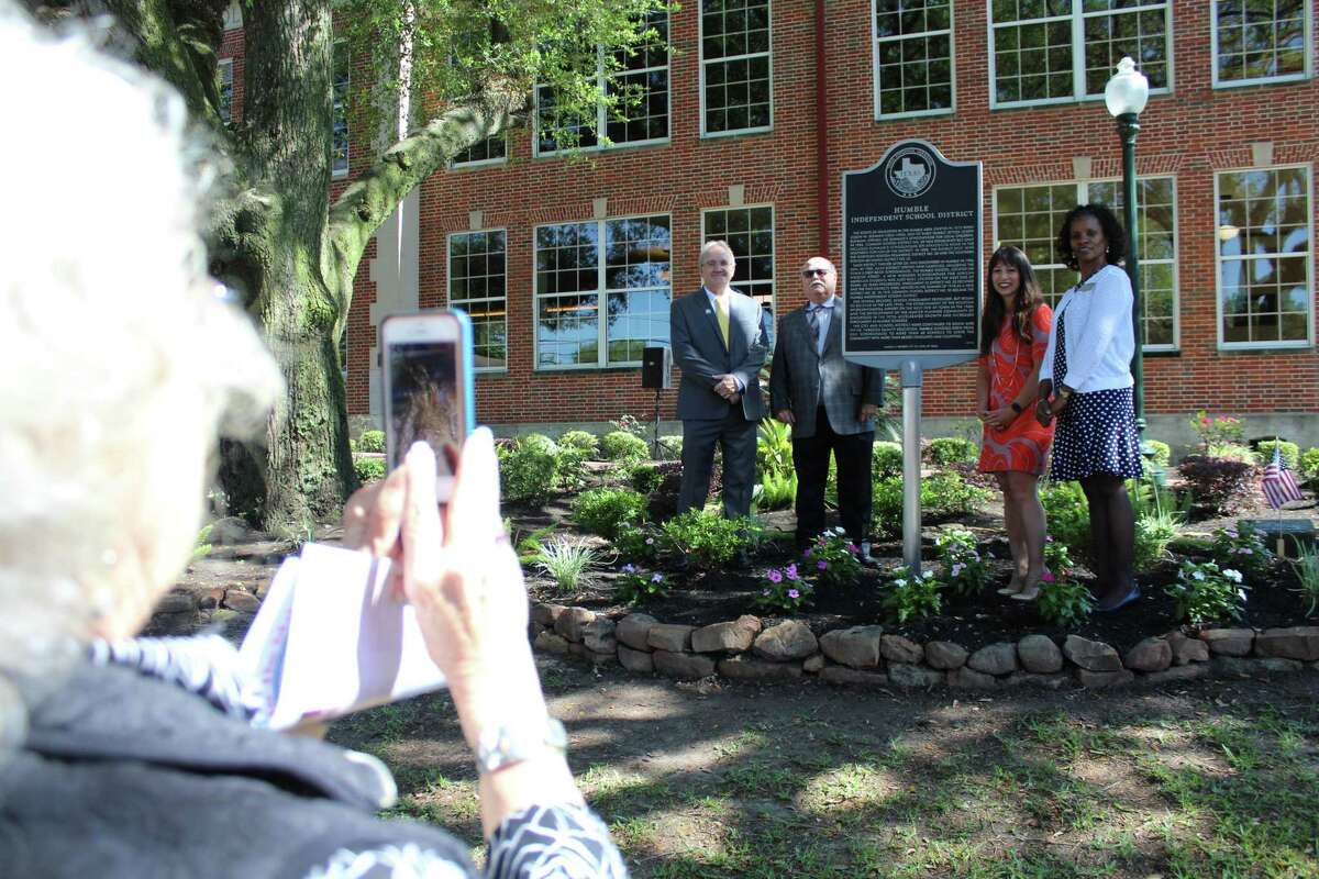Left to right: Paul Scott, Harris County Historical Marker Commission state marker chair; Robert Meaux, Humble ISD historian; Debra Blacklock-Sloan, Harris County Historical Commission marker dedication chair; and Elizabeth Fagen Humble ISD superintendent, unveil Humble ISD'S Texas Historical Marker celebrating 100 years in front of the Charles Bender Performing Arts Center on April 25, 2019.