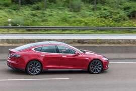 A 2016 Tesla Model S luxury cruises along a highway.