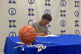 Kelly Catholic senior Chris May signs his National Letter of Intent on Thursday to play basketball at Dodge City Community College. Photo by Matt Faye/The Enterprise.