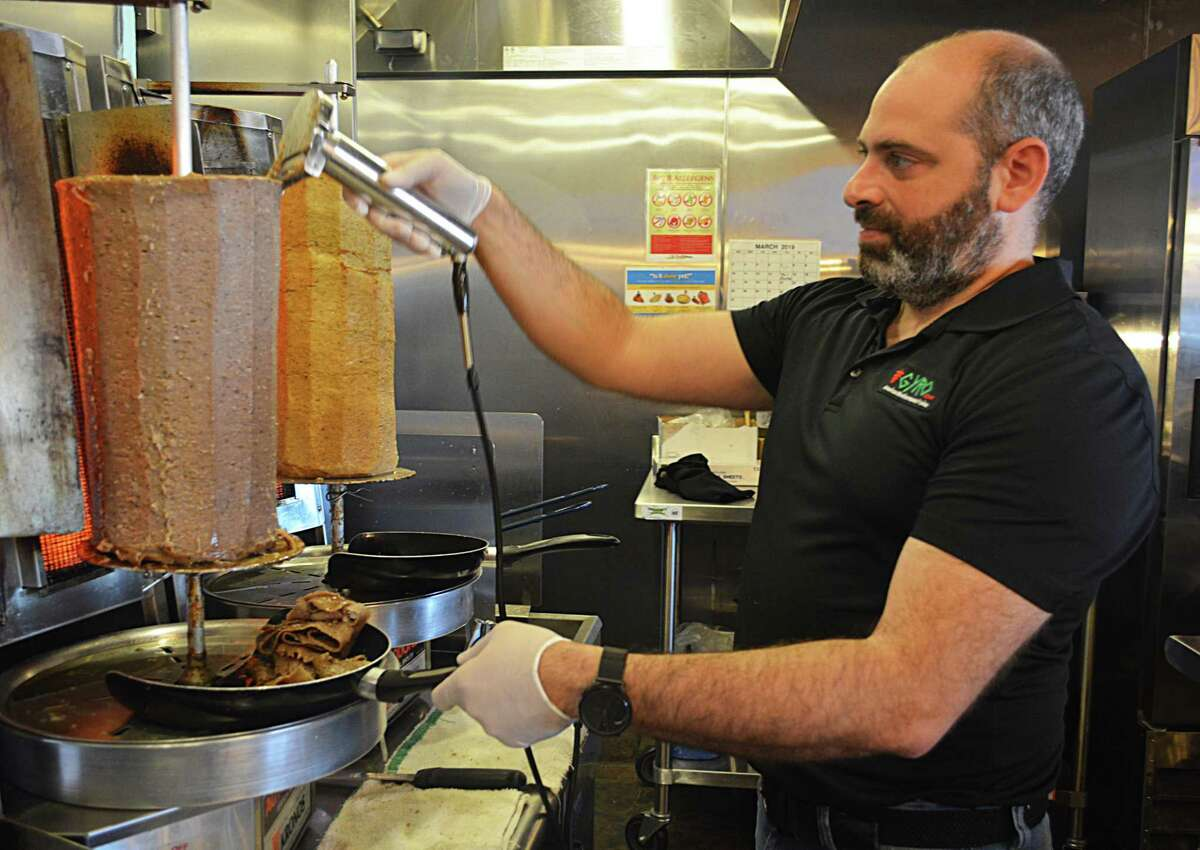 """Gyro Love, an American Mediterranean fusion eatery at 136 Berlin Road, in the Cromwell Commons shopping plaza, recently opened in a space shared with the wood-fired PizzaPie restaurant. William Mutraji, shown here shaving meat for a gyro, is partner in both enterprises. He aims to create a """"kitchen table""""-type dining atmosphere, and encourages customers to be adventurous with their menu choices by offering samples."""