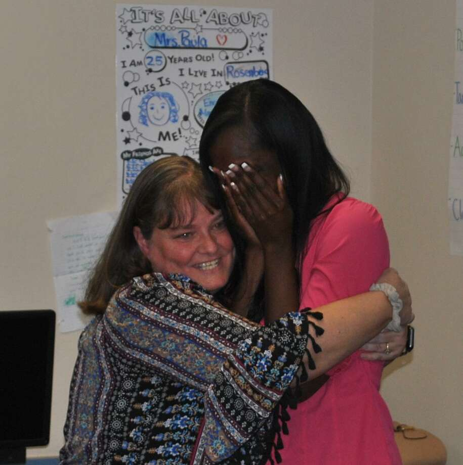 An emotional Tierra Shirley (right) celebrates her recognition with a Dickinson Elementary School colleague. Photo: Courtesy Photo