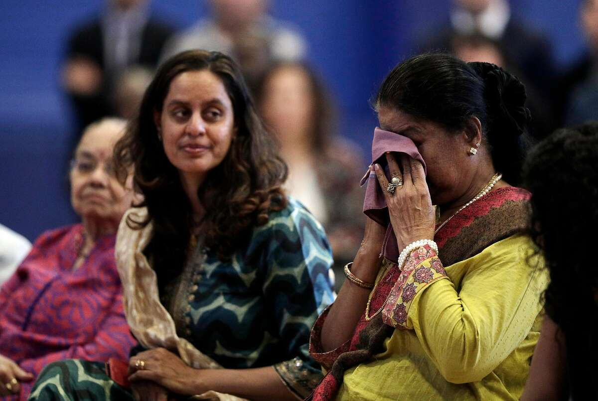 New San Francisco Public Defender Manohar Raju's mother Dhanam Raju, wipes away tears as her son Manohar Raju talks about his parents having grown up in India as his wife Asha Mehta listens during a swearing in ceremony at the Ella Hill Hutch Community Center in San Francisco, Calif., on Thursday, April 25, 2019.
