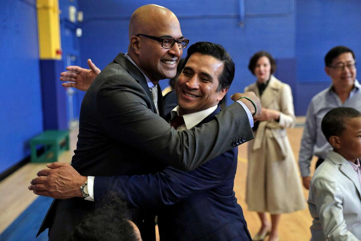 Hector Martinez, right, hugs new San Francisco Public Defender Manohar Raju following a swearing in ceremony at the Ella Hill Hutch Community Center in San Francisco, Calif., on Thursday, April 25, 2019.
