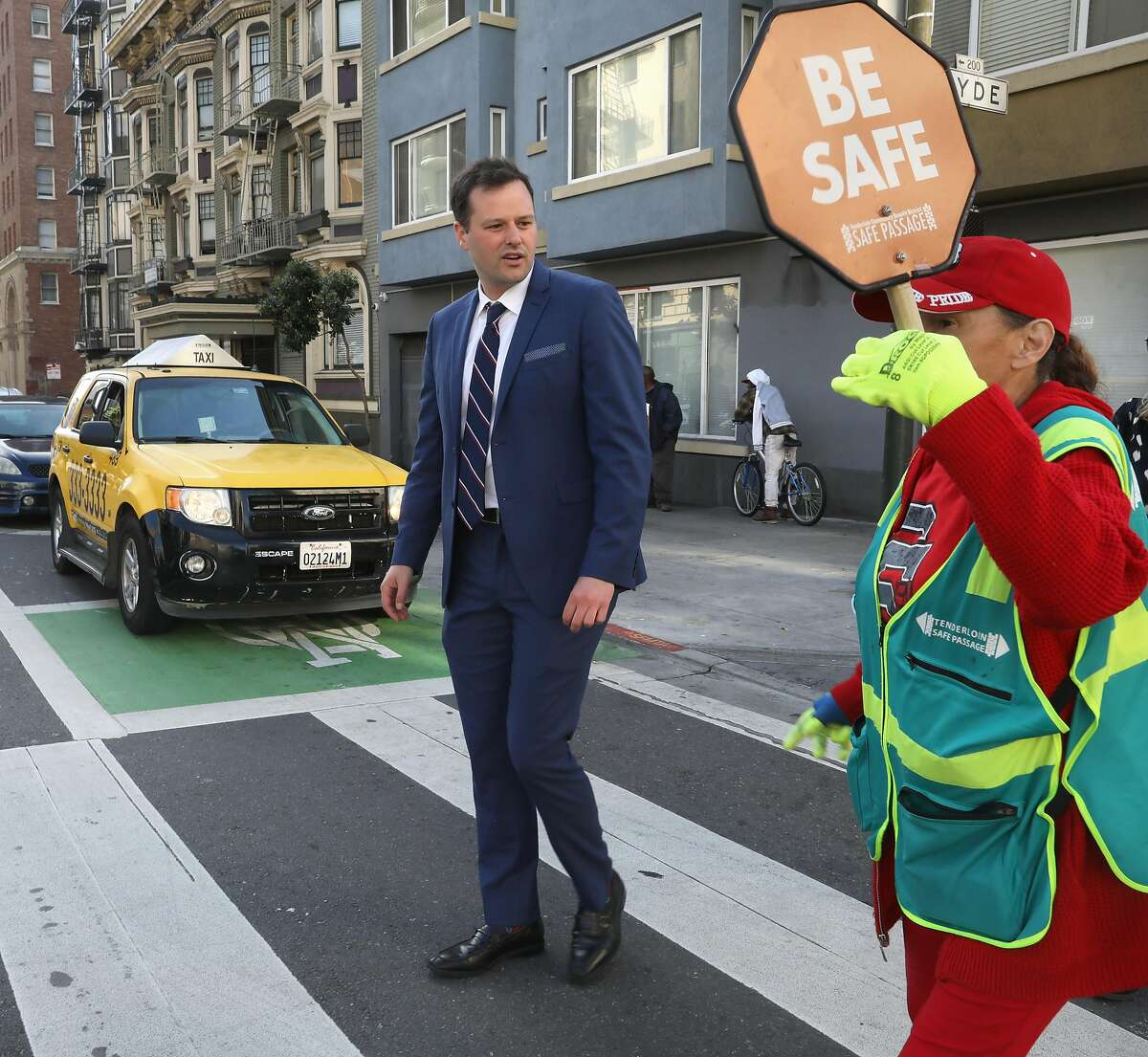 Supervisor Matt Haney (left) talks to traffic guard Sienna Noel (right) about sidewalk clean up in the tenderloin as she crosses him on Hyde St. on Wednesday, April 17, 2019, in San Francisco, Calif.