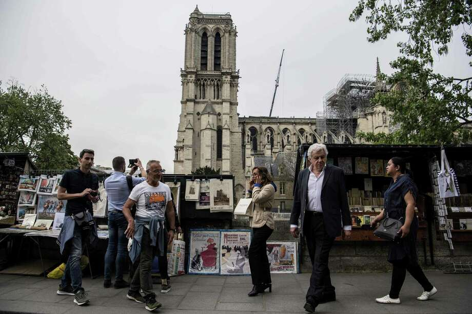 People walk on the opposite side of the Seine River overlooking the Notre-Dames de Paris Cathedral on Tuesday, following a major fire a week ago that destroyed the roof and spire. Photo: CHRISTOPHE ARCHAMBAULT /AFP /Getty Images / AFP or licensors