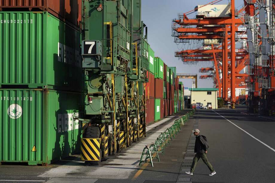 A man walks towards shipping containers stacked at a terminal in Tokyo, Japan, on Monday. After the U.S. withdrew from the multi-country Trans-Pacific Partnership, the U.S. is attempting to negotiate a deal solely between it and Japan. The TPP, however, went on without the U.S. and U.S. agriculture is losing out. Photo: Toru Hanai /Bloomberg / © 2019 Bloomberg Finance LP