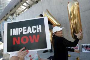 Frankie Wallace assembles a balloon display during an Impeach Donald Trump rally at 7th and Mission Streets outside of House Speaker Nancy Pelosi's office in San Francisco, on Monday. Democrats would be sorely disappointed after impeachment.