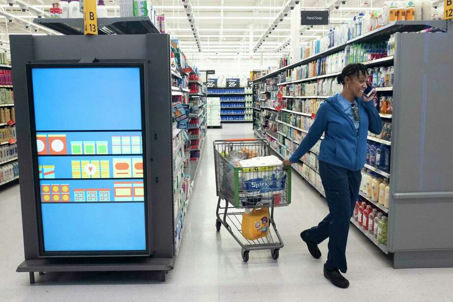 A customer pulls her shopping cart past an information kiosk at a Walmart Neighborhood Market, Wednesday, April 24, 2019, in Levittown, N.Y. Kiosks and signs throughout the store keep customers informed that they are shopping in an artificial intelligence factory. (AP Photo/Mark Lennihan) Photo: Mark Lennihan / Copyright 2019 The Associated Press. All rights reserved.