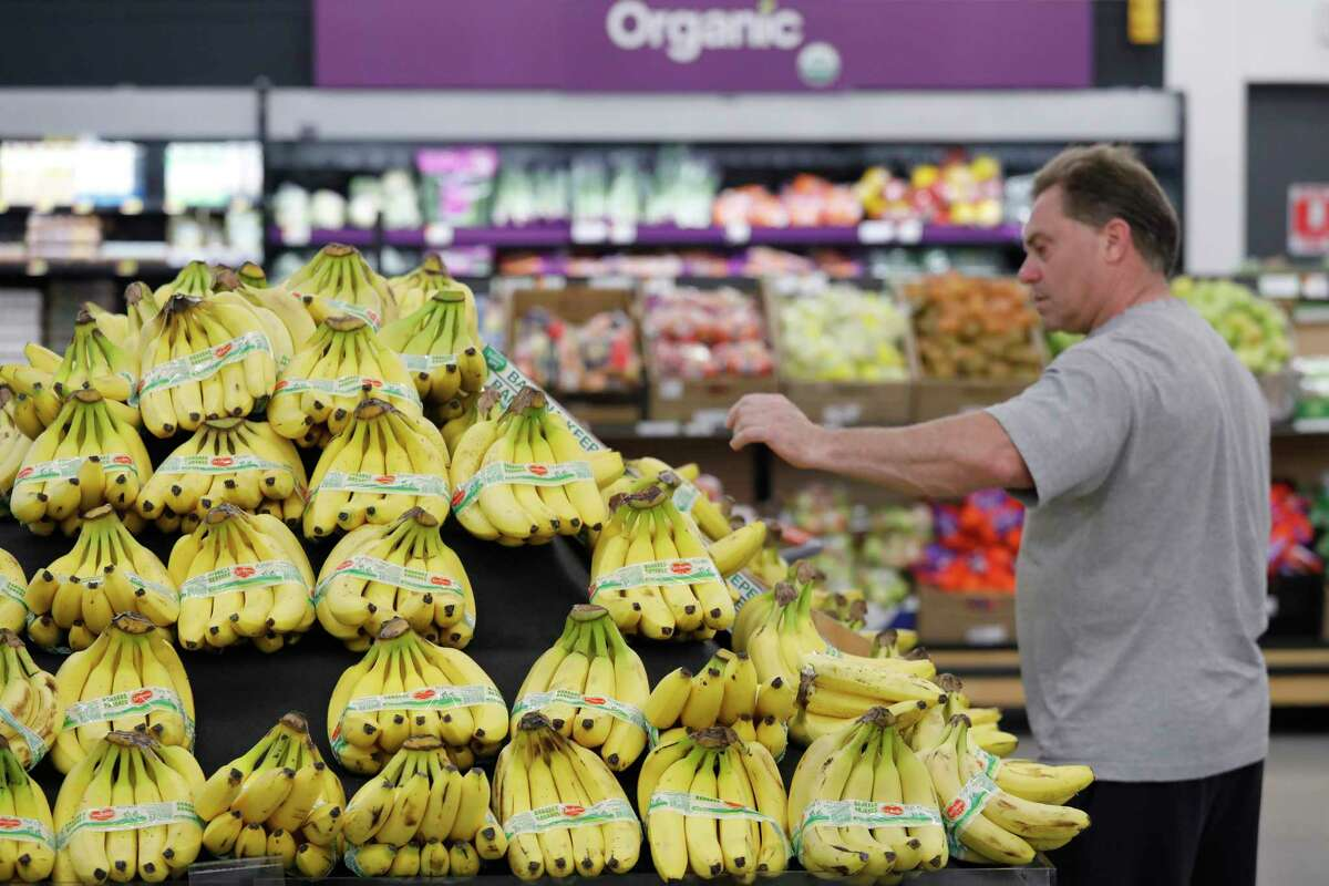 A customer shops for bananas at a Walmart Neighborhood Market, Wednesday, April 24, 2019, in Levittown, N.Y. High resolution cameras suspended from the ceiling point to the table of bananas and determine from the color of the bananas how ripe they are. When a banana starts to bruise, that would send an alert to an associate to replenish. (AP Photo/Mark Lennihan)