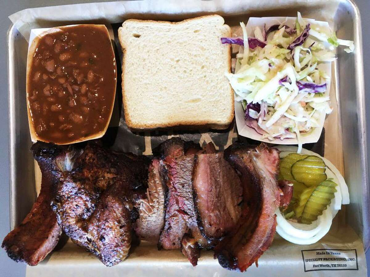 A three-meat barbecue plate from Brickyard BBQ that includes baby back ribs, smoked chicken, brisket, baked beans and coleslaw.