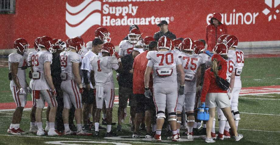 "The Houston Cougars offense huddles as the rain drenched them during the University of Houston's ""Friday night lights"" spring football practice, Friday, April 12, 2019, in Houston. Photo: Karen Warren/Staff Photographer"