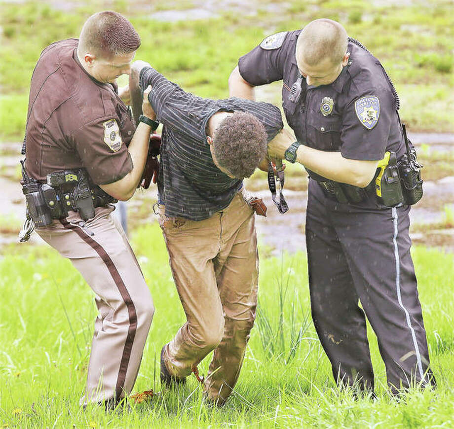A Madison County deputy sheriff, left, and an Alton police officer, right, help a juvenile up off the ground after he was arrested on the property of the former Alton Cine after eluding police for more than half an hour Thursday morning. Police broadcasts said the juvenile jumped from the back of an ambulance he was in, in the 4000 block of Humbert Road in Godfrey, touching off a search by more than a dozen officers from the sheriff's department and Alton police. Deputies called for a canine unit from Alton police and officers were searching the wooded area by a creek east of Humbert Road when the male youth was spotted walking and jogging up Humbert Road and onto the Farm & Home parking lot. When deputies arrived he continued running from them and across the Homer Adams Parkway until he was arrested on the former theatre parking lot. It was unclear why the youth was in the ambulance.