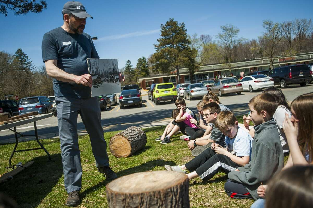 Kyle Bagnall holds up a historical photograph of a Michigan lumber camp during a presentation for Plymouth Elementary fourth graders by Dow Gardens staff in honor of Arbor Day on Thursday, April 25, 2019 at the school. (Katy Kildee/kkildee@mdn.net)