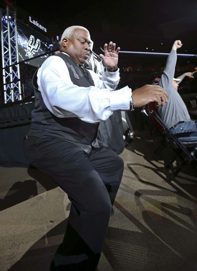 Eric Byrd, an Our Lady of the Lake employee, performs as the dancing usher with DJ Quake (David Gamez) in the background at the Spurs game against the Lakers at the AT&T Center on December 12, 2014. Photo: Staff File Photo