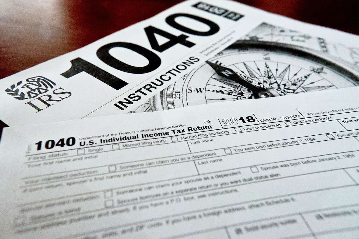 FILE- This Feb. 13, 2019, file photo shows multiple forms printed from the Internal Revenue Service web page that are used for 2018 U.S. federal tax returns in Zelienople, Pa. IRS data released Thursday, April 25, shows that while the average refund fell, the tax filing season was largely unchanged by the massive tax overhaul. (AP Photo/Keith Srakocic, File)