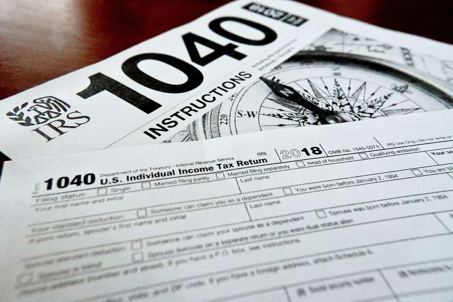 FILE- This Feb. 13, 2019, file photo shows multiple forms printed from the Internal Revenue Service web page that are used for 2018 U.S. federal tax returns. Photo: Keith Srakocic / Associated Press