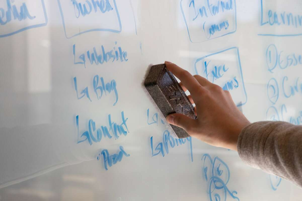 Taylor Huckaby, acting head of Communications, erase notes on the glass at WeWork for their online college on Wednesday, April 17, 2019, in Oakland, Calif.