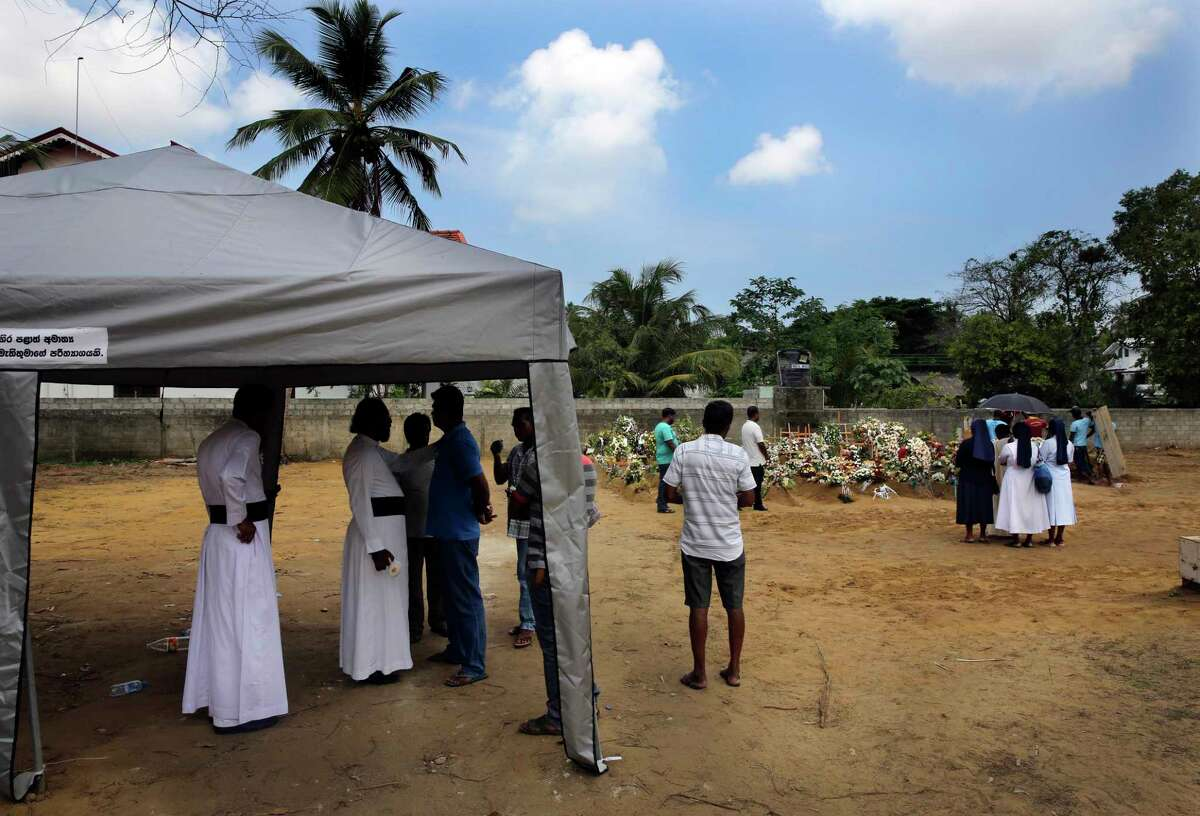 A Catholic priest talks to relatives of a Easter Sunday bomb blast victim at St. Sebastian Church, at a mass burial ground in Negombo, Sri Lanka Thursday, April 25, 2019. Sri Lanka has lowered the death toll from the Easter suicide bombings by nearly one-third, as authorities hunt urgently for a least five more suspects and brace for the possibility of more attacks in the coming days. (AP Photo/Manish Swarup)
