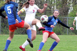 Roxana's Kortni Laws (7) tries to control the ball between Carlinville's Adrienne Welte (5) and Rory Drew 914) during Thursday's South Central Conference game in Carlinville. The Cavies won 3-1.