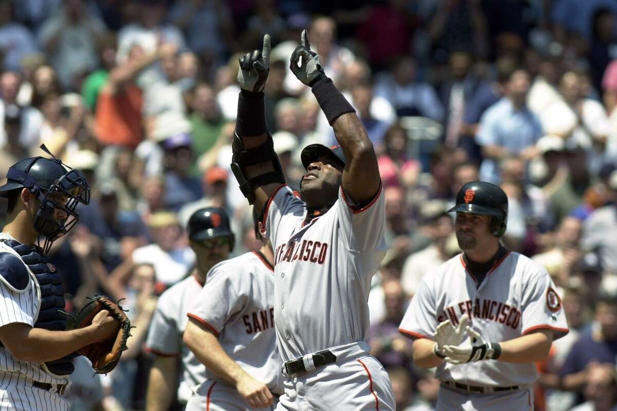 San Francisco Giants' Barry Bonds points skyward as he crosses home plate after hitting a three-run homer during the first inning of game against the New York Yankees at Yankee Stadium. The Giants defeated the Yanks, 4-3.