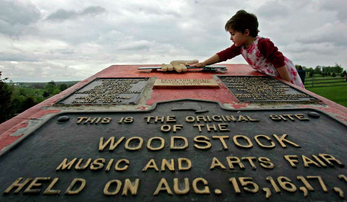 FILE - This May 15, 2008 file photo shows Emma Cenholt, 3, of Trumbull, Conn., playing on a memorial at the site of the Woodstock Music and Arts Fair in Bethel, N.Y. Woodstock 50 is less than four months away, but tickets for the event are still unavailable. Tickets for the three-day festival on Aug. 16-18 were supposed to go on sale Monday. The festival released a statement Thursday, saying: ?Woodstock 50 has delayed its on sale while we refine logistical plans.? (AP Photo/Mike Groll, File)